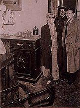 Entrando al comedor de la casa misteriosa acompañados de la policía. A los pies de Enrique Montroig Mendoza aparece una figurita decorativa de Minnie Mouse que acababa de caer al suelo desde lo alto de un aparador sin causa aparente. También aparece una silla que acababa de caer al suelo inexplicablemente. (Fotografía época inédita 1935).
