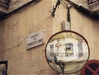 Esta calle, Francisco Giner, fue protagonista del segundo Expediente X español del siglo XX. En el espejo, el autor de este artículo en el momento de tomar la foto, y el letrero de carrer sobrepuesto.